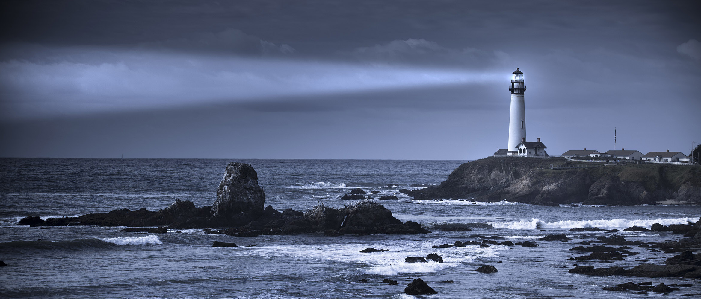 lighthouse on a rocky shore shining light over the ocean as a metaphor for insurance claims and loss control services