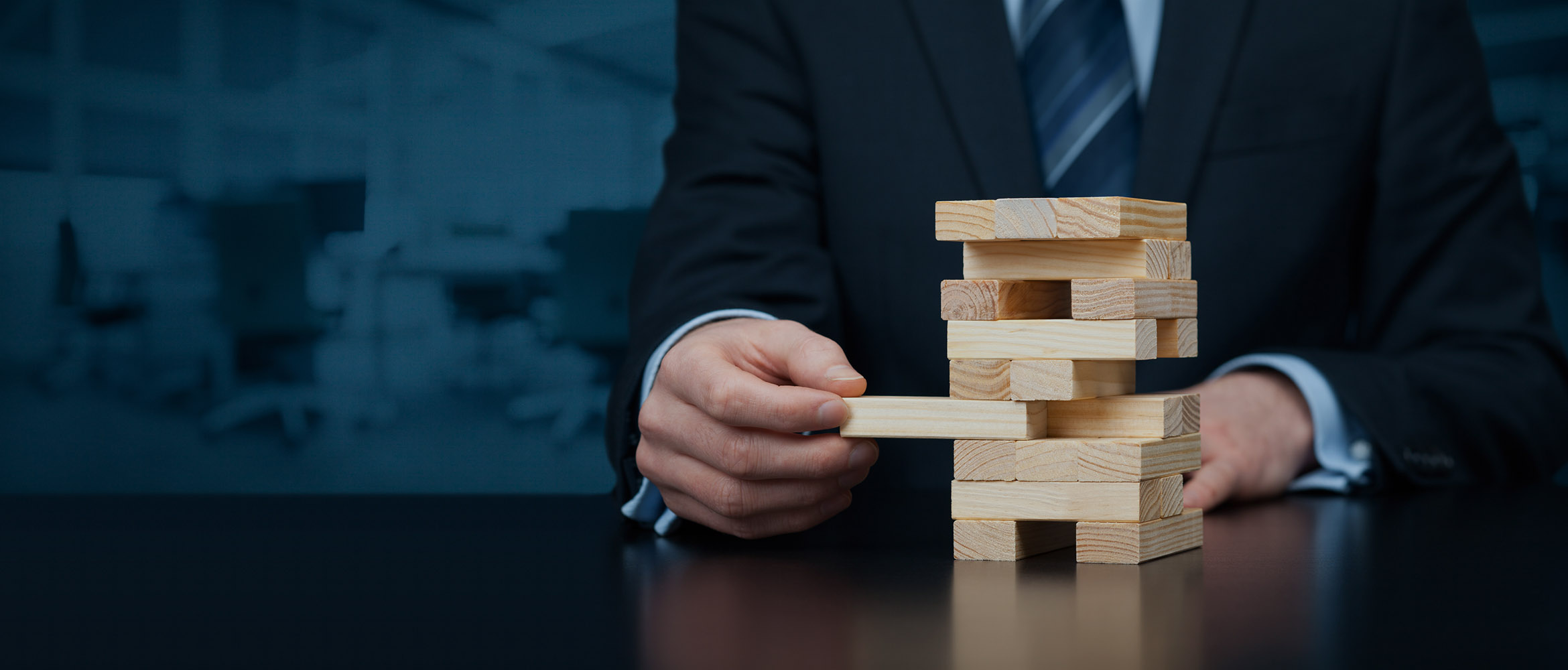 man in business suit removing block from block puzzle game as a metaphor for risk management related to commercial insurance