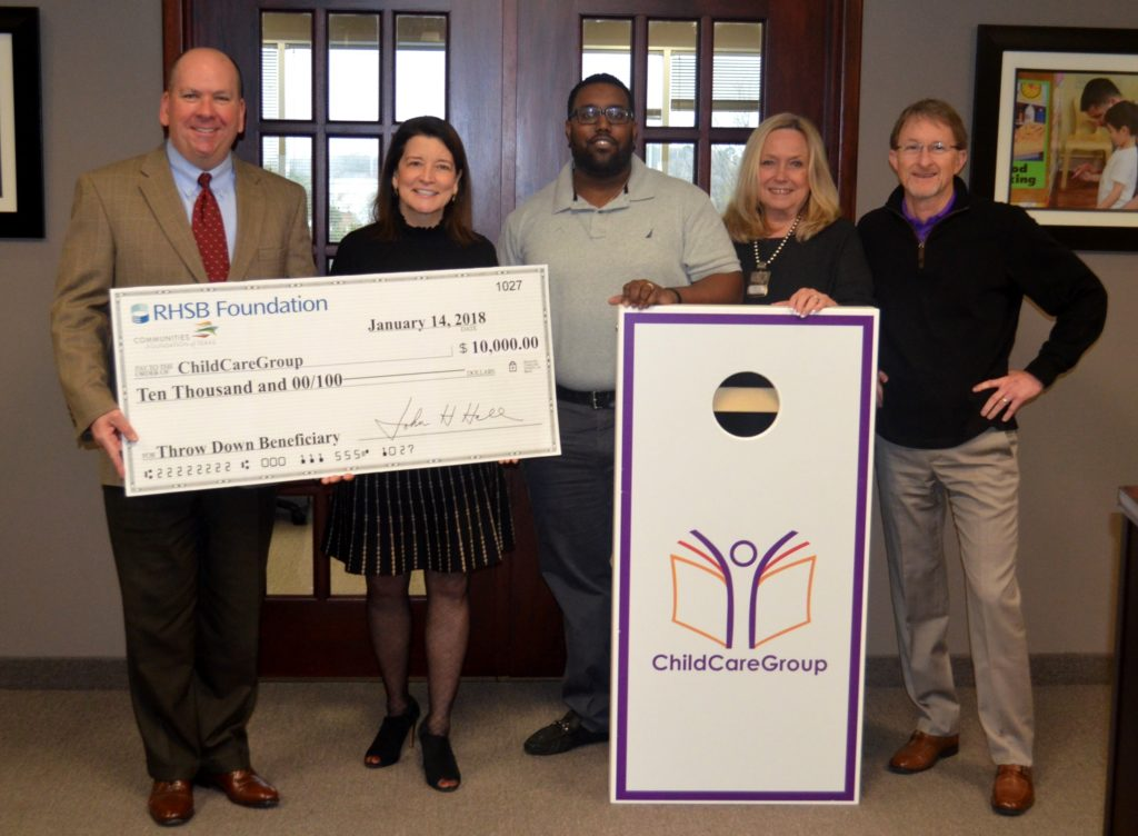 John Hall and Karen Farris present $10,000 check to ChildCareGroup pictured with cornhole board